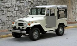 Fully restored 1971 Toyota LandCruiser FJ40 with a grey soft top. Equipped with both power steering and power disc brakes, it's had a few upgrades as a nod to modern convenience without losing its vintage bona fides. Paint quality is outstanding; the