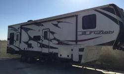 This Toy Hauler has never hauled a ATV or Motorcycle like their built for. Used maybe 10 times, this trailer has two slide outs with two queen beds in garage on motorized tracks, with picnic style table in lower bed for inside outside dinning. Screen