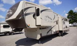 The 2013 Big Country 3251TS is a fifth wheel that comes with three slides and a large sofa that lines the back. Two chairs and a table and chairs are included in a rear slide. An entertainment center is part of this floor plan as are a stove,