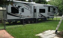 This fifth wheel camper is in great condition, only been used a few times, has a new flat screen tv in the living area, has two pull down beds that can also be made into a dining room table, it has three awnings, has three slide outs, and has the locking