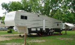 """This is a 45ft 5th wheel, it will sleep 7 people comfortably. It has 2 bedrooms & 2 full baths. (Master bath has a garden tub). It is much like a house, featuring high ceilings with a ceiling fan, fire place, Vinyl Flooring in Kitchen, 50"""" flat screen TV"""