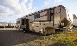 The 2015 Gateway 3900SE is a fifth wheel that has four slides along with a rear sofa, two chairs and an entertainment center. The kitchen area includes a refrigerator, stove, microwave, an island counter with a double sink and dinette with seating. The