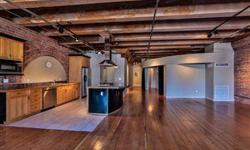 This is a true loft home with dramatic high, beamed ceilings, exposed brick walls, original fir plank floors, and over-sized windows with eastern and southern exposures. The airy, open floor plan, features a kitchen with granite counter tops, stainless