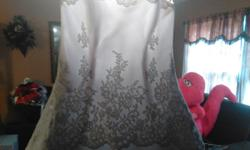 A White and Silver Lace trimmed Gown with pearls on the Bodice. Size 16. Very Beautiful ,Clean too. Call today for viewing and Tryon..