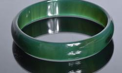 """A dark green jade bangle bracelet featuring a smooth finish. It measures 3"""" across. *This item has verified by an independent GIA"""