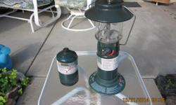Propane lantern with auto light feature and a spare propane cylinder.