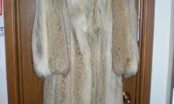 This coat of Cayote pelts is styled with a full length, straight sleeves and a shawl collar. Appraised at $5,300. Size 10/12