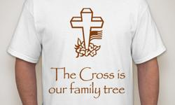 """The shirt is white with a cross and says """"The Cross is our family tree""""."""
