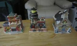 Cute Christmas village buildings/houses for sale. There are a total of 21 pieces to choose from. There are 9 large buildings and 12 smaller buildings. Price is $2 for the larger buildings and $1 for the smaller ones. The larger buildings are shown in the