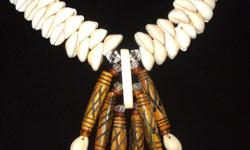 This beautiful necklace is brand new, never worn, artisan quality and gorgeous. It's made with cowrie shells and carved bone pieces and crystals. It's 17-1/2 inches long. Kat