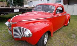 1941 Business Coupe red. The engine is 360 cubic inch, rebuilt 2013, 727 transmission. Power front disk brakes, rack and pinion power steering, air conditioning, custom build stainless steel headers by Kooks, custom built radiator, dual fans, torque