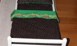 ANTIQUE WOODEN DOLL BED, with new bedding, covers are in black background with red apples and green leaves, bed has handpainted decoration,and is cream colored. Must See to appreciate, very colorful, and want show soiling easily. Make
