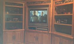 Entertainment Center with storage units. Underneath storage. Honey color with decorative leaf design.Cabinet lights included. Can separate three units. In great condition. Purchased from Hom Furniture.