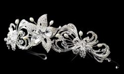 A floral headpiece that is simply stunning. Featuring a exquisite floral accents with swirl and leaf designs throughout the head piece with rhinestones encrusted on silver plating plus freshwater pearls and Swarovski crystal scents. This headpiece is