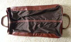 RICH MEDIUM BROWN NAUGAHYDE ZIPPERED GARMENT BAG. LOOKS LIKE LEATHER. BAG IS 40 IN. LONG BY 22 IN. WIDE. FULL LENGTH ZIPPER DOWN THE FRONT AND 14 BY 18 INCH ZIPPERED COMPARTMENT IN THE BACK, GREAT FOR SHOES. BAG HAS TWO HANDLES FOR CARRYING,