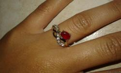 I brought this ring for my girlfriend and it ended up being way too big. The stone is genuine garnet the birthstone of January, its a gold plated ring with clear stone along the design that look like diamonds. I don't know the size but its probably up