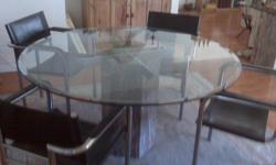 Beautiful round glass table and 6 leather and chrome chairs, including the matching side board for sale. Table is round 55 inches in diameter height 28 inches sideboard top is glass and measures approximately 51 inches long, 15 inches deep and 28 inches