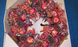 """Decorator style wreath done in """"pinkish/red"""" colors consisting of Berries, Pomegrantes, leaves, etc. 24x24 dimension Upscale and new in box. (estimated value $ 100.00) Riverview area."""