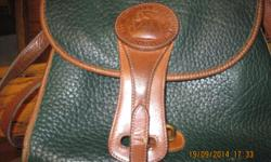 Green purse is made by Dooney & Bourke. Is a all weather leather. The purse is used but has no rips, tears, or stains. The purse has some wear on it. Asking for $20.00 or OBO.