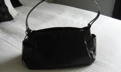 Hobo brand black leather handbag. Dimensions of bag are 13 in length, 5 in wide, and 7 1/2 in tall. Has a small pocket on each end that work well for a cell phone. Call -- to arrange a time to buy!