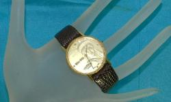 This timepiece features Lady Liberty on its watchface in gold tones. It has the dates 1886-1986 to commemorate the coin. On the face is the maker's name Dufonte Quartz, swiss made by Lucien Piccard. Dufonte is a subdivision of Lucien Piccard, one of the