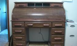 Roll top desk oak for sale. Numerous drawers and slots for storage. Light inside roll top area.