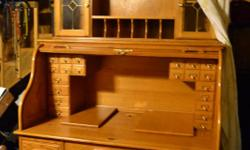 LARGE OAK ROLL TOP DESK, 6 1/2H 4 FT W 3 FT DEEP. EXCELLENT CONDITION. VERY HEAVY, NEED MUSCLE TO MOVE. PLENTY OF DRAWERS AND CUBBY HOLES AND EXTRA CABINET ON TOP WITH GLASS DOORS. COMPUTER COMPATABLE TOO.