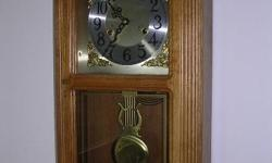 Oak cabinet wall clock with glass door. Large Brass Pendulum with chimes. This is a windup clock and has key to wind it up. Excellent condition. May be seen in Concord, MA or Londonderry, NH