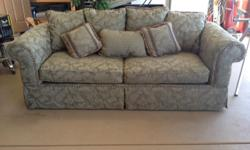 Olive green brocade sofa (7.5 feet in length). Like new (housed in a front room area where there was minimal use). Three large cushions cover seat area. Back is covered with assorted sized matching cushions. Arms are rolled. Robe trim on cushions