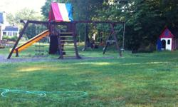 Rainbow Playground. Monster castle package. Four swings, monkeybars, rockwall, tire swing, trapeze, slide and rope swing. Excellent condition. Wooden playhouse fits 4-6 small children. Loft upstairs. Base material for