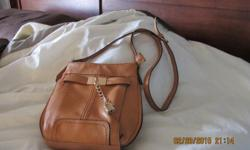 Tan purse with gold trim; adjustable body strap; new