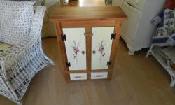 natural color wood w/floral design on door fronts and bottom. measures-32 inches tall. 23 inches wide. 10 1/4 inches deep. shows slight wear(light scratches), but in very good condition overall. the background in the painted area is a creamy/pale yellow