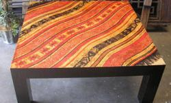 A small square coffee tablemade of MDF, a wood product, decorated with a paper collage techniquedesign. Never used. Good condition. Measures: 43 w x 43 d x 18 h. Pueblo Indio Furniture, Argentina