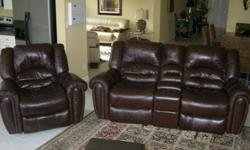 Brown leather matching duo console sofa and chair, new condition. Purchase price $2010.72 Chair rocks,swivels and reclines to sleeping position. Console Sofa has 2 recliners that also rocks.