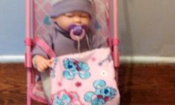 Baby doll cries and laughs and uses pacifier like a real baby. All in good used condition.