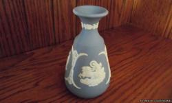 This 5 inch tall vase was made by the famous Wedgewood of Stoke on Trent, Staffordshire England. It is of blue jasper or jasperware with white applied jasper classical figures and the date 1976. There is Cupid Asleep, Apollo and his chariot and Pegasus.