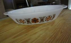 """Very nice Glasbake white divided casserole. Has brown and orange pattern on sides. Bottom is marked """"J2352,"""" """"Glasbake,"""" and """"USA."""" Measures approximately 12 long, 9 inches wide and 3 inches high. Top edges are rough on the long sides of the casserole."""