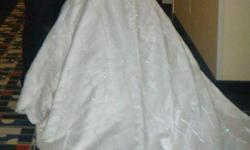 Beautiful ivory wedding dress with lots of pearls, detailed beading and a long train. Worn once, cleaned and professionally hand-washed due to delicate crystals and beading. In excellent condition. Comes with veil, unique hand-made bouquet and