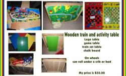 """WOODEN TRAIN AND ACTIVITY TABLE   IS ON WHEELS AND CAN ROLL UNDER A CRIB OR BED 10"""" HIGH GENTLY USED BUT ON GREAT CONDITION LEGO TABLE  CHALK BOARD  GAMES"""